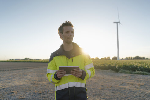 Engineer standing in rural landscape at a wind turbine holding tablet - GUSF01348