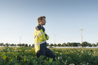 Engineer standing in a field at a wind farm - GUSF01354