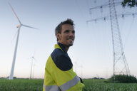 Smiling engineer next to a wind farm and power pole - GUSF01357