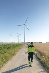 Engineer walking on field path at a wind farm - GUSF01363