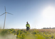 Engineer standing in a field at a wind farm - GUSF01366