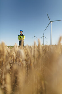 Engineer standing in a field at a wind farm - GUSF01369