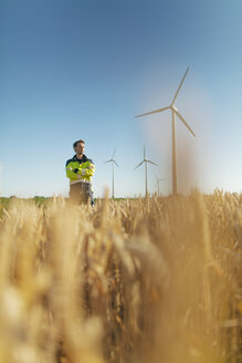 Engineer standing in a field at a wind farm - GUSF01372
