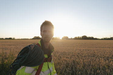 Technician with climbing equipment at a field in sunset - GUSF01375