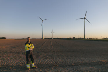 Engineer standing in a field at a wind farm - GUSF01378