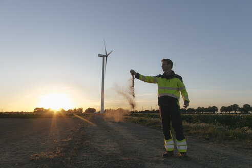 Engineer at a wind turbine at sunset scattering soil - GUSF01381