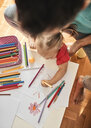 Little girl drawing with coloured pencil while her father watching her, top view - ZEDF01756