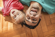 Portrait of father and little daughter lying on the floor at home having fun - ZEDF01765