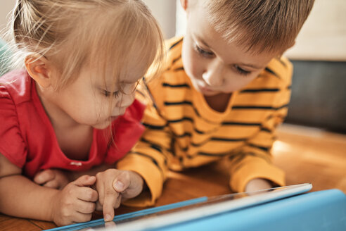 Brother and little sister lying on the floor at home using digital tablet - ZEDF01768