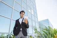 Businessman using tablet outside office building - KIJF02094