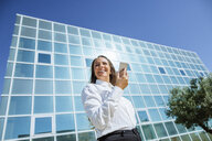 Smiling businesswoman using cell phone outside office building - KIJF02100