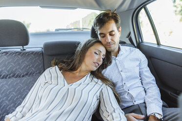 Woman sleeping on back seat of a car leaning against man - KIJF02112