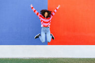 Happy young woman jumping in the air - KIJF02121