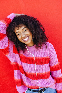 Portrait of laughing young woman with earphones in front of red wall - KIJF02124