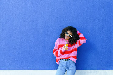 Portrait of smiling young woman with bottle of orange juice standing in front of blue wall - KIJF02127