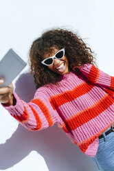 Portrait of young woman wearing sunglasses taking selfie with mobile phone - KIJF02130