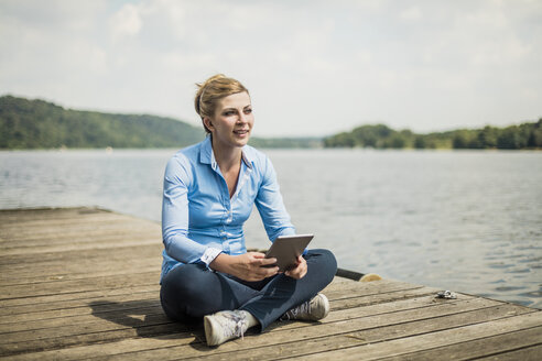 Woman sitting on jetty at a lake using tablet - MOEF01485
