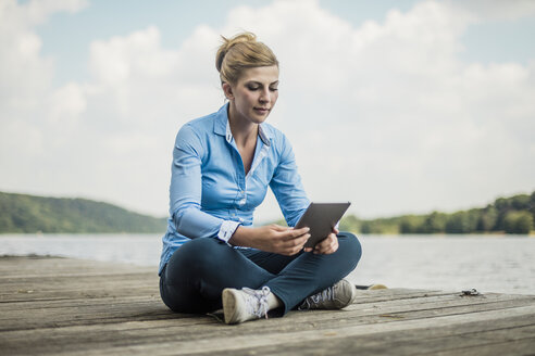 Woman sitting on jetty at a lake using tablet - MOEF01488