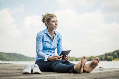 Woman sitting on jetty at a lake using tablet - MOEF01491