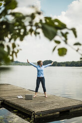 Woman stretching on jetty at a lake next to laptop - MOEF01497