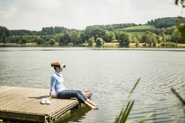 Woman with VR glasses sitting on jetty at a lake with feet in water - MOEF01500