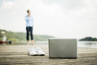 Laptop and shoes on jetty at a lake with woman in background - MOEF01503