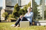Woman wearing headphones sitting on urban meadow next to laptop - MOEF01515