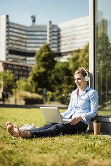 Smiling woman wearing headphones sitting on urban meadow using laptop - MOEF01518
