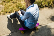 Woman sitting on penny board talking on cell phone - MOEF01521