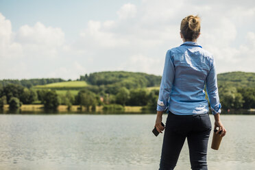 Woman standing at a lake with cell phone and takeaway coffee - MOEF01524