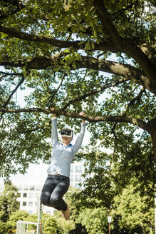 Woman in urban park hanging at branch of a tree wearing VR glasses - MOEF01527