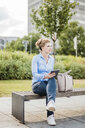 Woman sitting on a bench holding tablet - MOEF01530