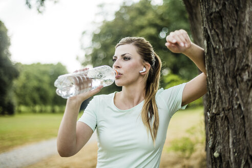 Sportive young woman leaning against a tree in a park drinking from bottle - MOEF01536