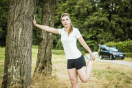 Sportive young woman stretching at a tree in a park - MOEF01539
