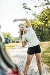 Sportive young woman stretching and using cell phone at a car in a park - MOEF01548