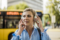 Portrait of smiling woman in the city wearing headphones - MOEF01557