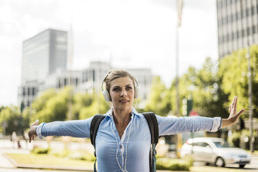 Smiling woman with backpack in the city wearing headphones - MOEF01560