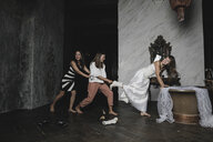 Playful friends and bride during wedding preparation - KMKF00619