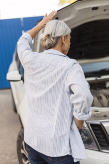 Back view of senior woman looking at car engine - VGF00104