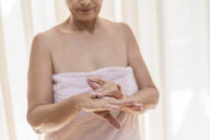 Senior woman applying cream on hand in the morning - VGF00107