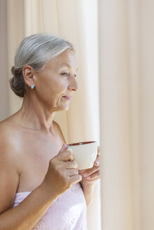 Senior woman wrapped in towel drinking cup of coffee in the morning - VGF00110