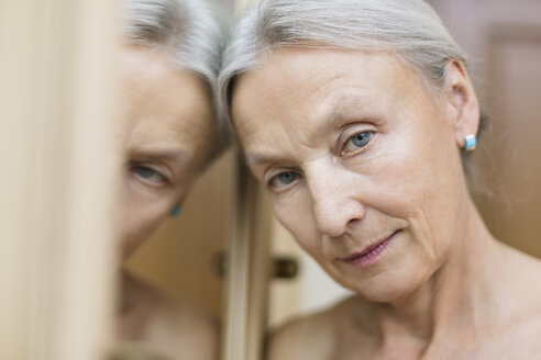 Portrait of senior woman leaning against mirror - VGF00113