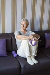 Portrait of pensive senior woman sitting on the couch with knitting looking at distance - VGF00116