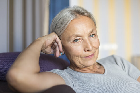 Portrait of smiling senior woman relaxing on the couch at home - VGF00122