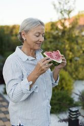 Senior woman eating watermelon slice in the garden - VGF00131