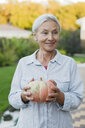 Portrait of smiling senior woman with harvested pumpkin in the garden - VGF00134