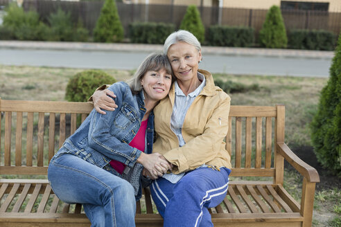 Portrait of senior woman sitting together with her adult daughter on a bench - VGF00137