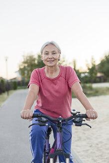 Portrait of smiling senior woman riding bicycle - VGF00140