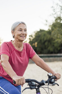 Portrait of smiling senior woman riding bicycle - VGF00143