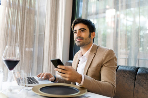 Smiling man sitting at table in a restaurant using laptop and cell phone - VABF01646